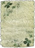 Parchment paper scrolls with shamrock. Vintage grunge textured parchment scroll with four leafed clover, antique background texture of a paper page Stock Photography