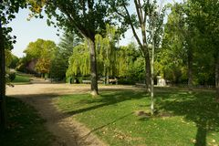 Parco con gli alberi ed i banchi lungo la riva fotografie stock