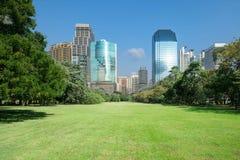 Parco della città con il fondo moderno della costruzione Fotografia Stock
