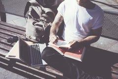 Parco della città della maglietta bianca dell'uomo della foto del primo piano e taccuino di seduta d'uso di scrittura Studiando a Immagini Stock Libere da Diritti