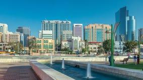 Parco della spiaggia del boulevard di Corniche lungo la linea costiera nel timelapse di Abu Dhabi con i grattacieli su fondo stock footage