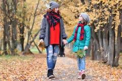 Parco di autunno della passeggiata della donna e della figlia della famiglia Immagini Stock Libere da Diritti
