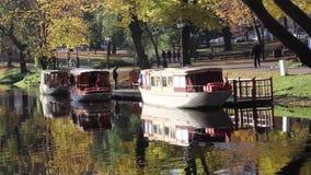 parco di autunno delle barche turistiche nel centro canale di Riga, Lettonia che attraversa l'autunno del parco del bastione archivi video