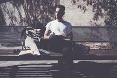 Parco di seduta d'uso della città della maglietta bianca dell'uomo della foto e scrivere il libro di messaggio Studiando all'univ Immagini Stock