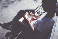 Parco di seduta della città dell'uomo della foto e blocco note mandante un sms del messaggio Studiando all'università, progetto d Fotografia Stock