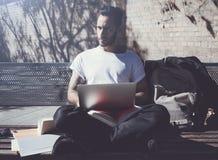 Parco di seduta della città dell'uomo della foto e taccuino mandante un sms del messaggio Studiando all'università, preparazione  Fotografia Stock Libera da Diritti