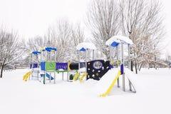 Parco di Snowy con le oscillazioni e gli alberi immagine stock