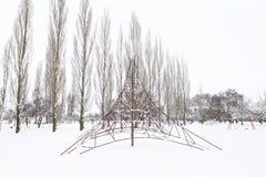 Parco di Snowy con le oscillazioni e gli alberi fotografia stock