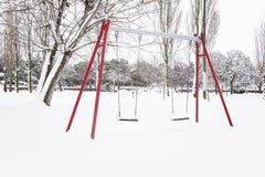 Parco di Snowy con le oscillazioni e gli alberi fotografia stock libera da diritti