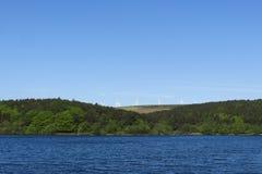 Parco eolico e lago nel paesaggio di estate Immagine Stock