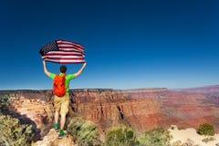 Parco nazionale ed uomo di Grand Canyon con la bandiera degli Stati Uniti Fotografia Stock