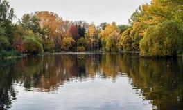 Parco variopinto di autunno e la sua riflessione in uno stagno alla sera nuvolosa Immagini Stock