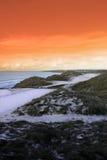 Parcours ouvert de golf avec le ciel orange de coucher du soleil de l'hiver Images stock
