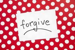 Pardonnez - le mot sur le vrai papier blanc avec le rouge et le fond de points, la religion et les relations photographie stock