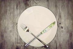 Pare comen concepto Tabla de madera con la placa vacía y los cubiertos de plata cruzados que simbolizan para rechazar la comida Imagenes de archivo