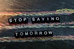Pare de dizer amanhã em blocos de madeira Imagem processada transversal com fundo do quadro-negro imagem de stock
