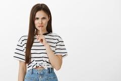 Pare de falar, feche acima Retrato da mulher europeia nova insultada irritada com cabelo marrom e o t-shirt listrado, olhando de  Fotos de Stock Royalty Free