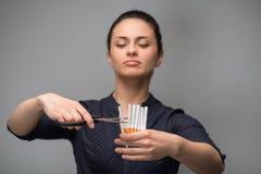 Pare de fumar o conceito Cigarros do corte da jovem mulher Imagens de Stock