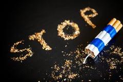 Pare de fumar o conceito no fundo com cigarros quebrados heap imagens de stock