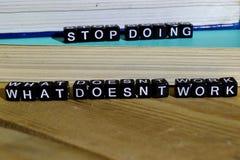 Pare el hacer de qué trabajo del ` t del doesn sobre bloques de madera Concepto de la motivación y de la inspiración imagenes de archivo