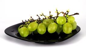 Pare el movimiento del manojo de uvas verdes en la placa negra