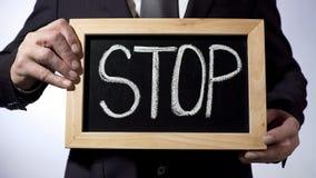 Pare escrito en la pizarra, persona del negocio que lleva a cabo la muestra, motivación, honradez Imagenes de archivo