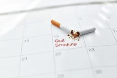 Pare a imagem anti-fumaça rendida Smoking Feche acima de cigarro quebrado que encontra-se no calendário Fotografia de Stock