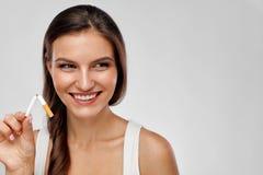 Pare a imagem anti-fumaça rendida Smoking Mulher feliz bonita que guarda o cigarro quebrado Imagens de Stock Royalty Free