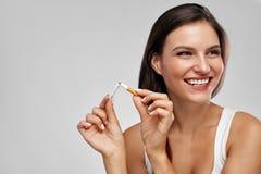 Pare a imagem anti-fumaça rendida Smoking Mulher feliz bonita que guarda o cigarro quebrado Imagens de Stock