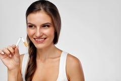 Pare a imagem anti-fumaça rendida Smoking Mulher feliz bonita que guarda o cigarro quebrado Foto de Stock