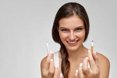 Pare a imagem anti-fumaça rendida Smoking Mulher feliz bonita que guarda o cigarro quebrado Foto de Stock Royalty Free