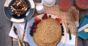 Pare la opinión de movimiento de un desayuno de crepes con las bayas y las frutas secas almacen de metraje de vídeo