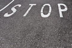 Pare la palabra en el asfalto Foto de archivo libre de regalías