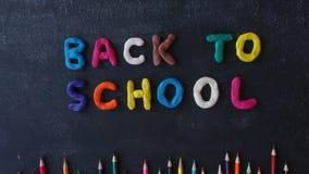 Pare las letras hechas a mano del plasticine del movimiento de nuevo a escuela en la pizarra Arcilla de modelado del arco iris de metrajes