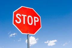 Pare o sinal de encontro ao céu azul Fotos de Stock Royalty Free