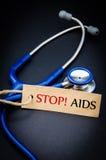 Pare SIDA en la etiqueta de papel con el estetoscopio Fotografía de archivo libre de regalías