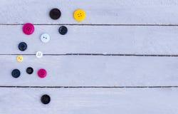 Parecchi bottoni multicolori su un fondo di legno Fotografia Stock
