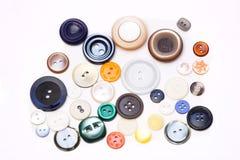 Parecchi bottoni su un fondo bianco Fotografia Stock Libera da Diritti