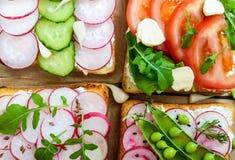 Parecchi generi di panini con le verdure: ravanello, pomodori, cetriolo, rucola su pane tostato croccante Immagini Stock