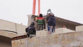 Parecchi lavoratori maschii addetti all'azione intorno a beem concreto sollevato enorme archivi video