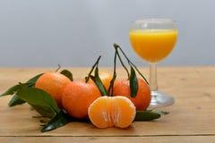 Parecchi mandarini con un vetro di succo fotografia stock