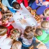 Parecchi piccoli bambini attingono un foglio di carta con le matite Una vista da sopra fotografia stock libera da diritti