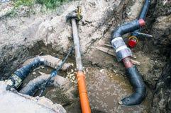 Parecchi tubi nella fossa di terra per il sistema di riscaldamento Immagine Stock