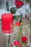 Parecchi vetri di vino rosato nella priorità alta, nei fiori, nei dolci e negli spuntini alla tavola festiva, sono aumentato, vet Immagine Stock