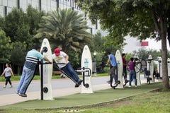 Parecchia gente che si esercita in un'area di forma fisica di un parco pubblico fotografie stock libere da diritti