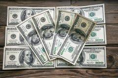 Parecchie banconote di 100 dollari, diffusione fuori su una superficie di legno invecchiata Immagine Stock Libera da Diritti