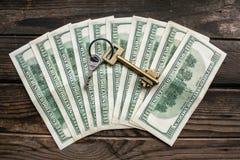 Parecchie banconote di 100 dollari nella disposizione del semicerchio con una chiave domestica sulla superficie di legno approssi Immagini Stock Libere da Diritti