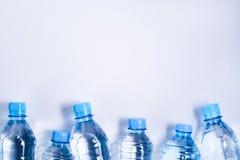 Parecchie bottiglie di acqua beventi su fondo bianco immagini stock libere da diritti