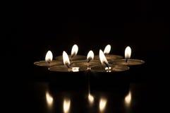 Parecchie candele su un fondo scuro riflesso fotografie stock