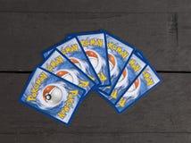 Parecchie carte molto popolari di Pokemon su fondo di legno scuro Fotografia Stock Libera da Diritti
